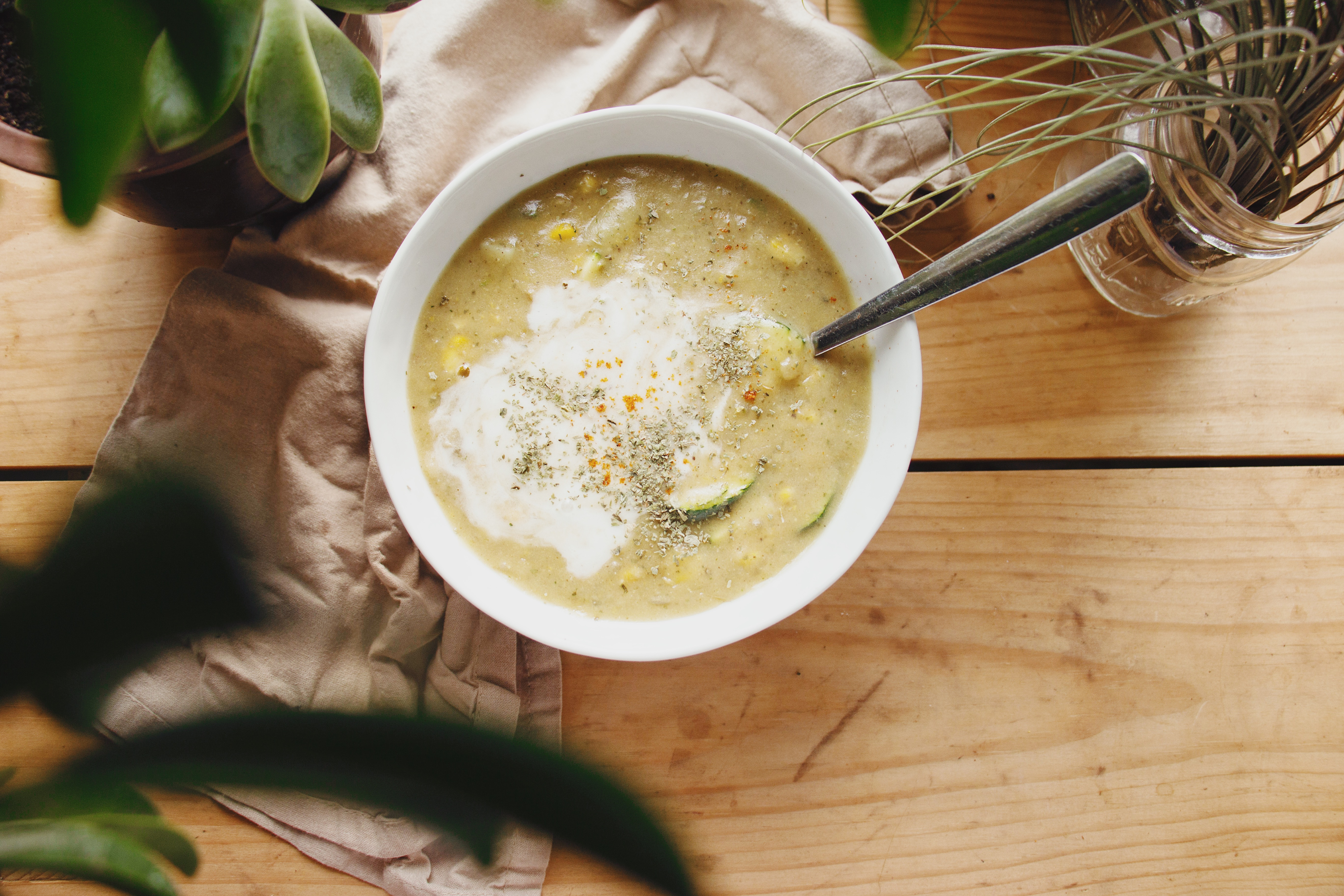 Summer corn chowder in white bowl with spoon